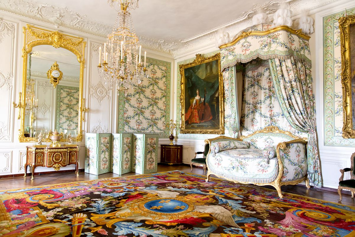 A room with large gilded mirror and artwork on the walls, and a daybed.
