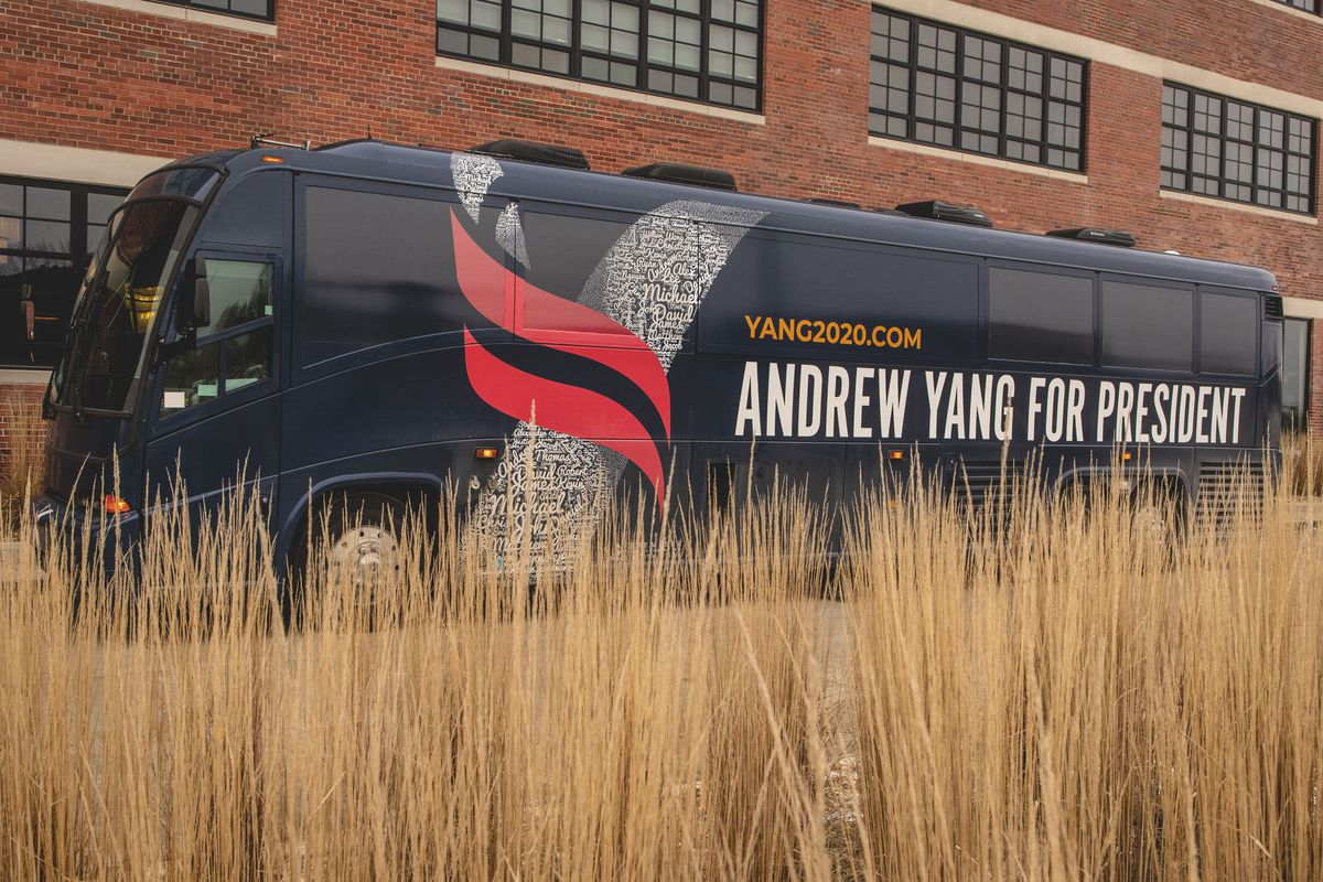 """Campaign bus with """"Andrew Yang for President"""" written on the side parked alongside a building,"""