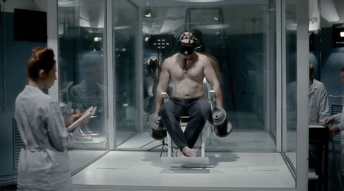 A seated, shirtless, shoeless, masked man in a glass box lifts weights while a uniformed woman observes and takes notes.