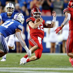 Utah Utes quarterback Charlie Brewer (12) slides down with Brigham Young Cougars linebacker Keenan Pili (41) moving in as BYU and Utah play an NCAA football game at LaVell Edwards Stadium in Provo on Saturday, Sept. 11, 2021.