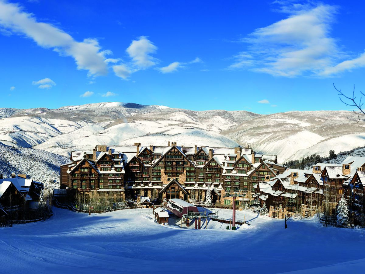 A wide shot of a large mountain hotel at the base of a ski area and four-person chairlift. The lodge is covered in snow and there are snowy hills behind the resort.