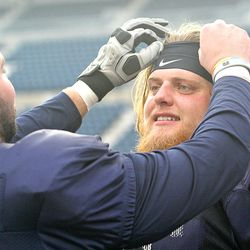 USU center Quin Ficklin, left, fixes the headband of fellow offensive lineman Roman Andrus following the Aggies' practice on Dec. 19 at Maverik Stadium. Ficklin and Andrus originally became friends while teammates at BYU before reuniting this season in Logan.