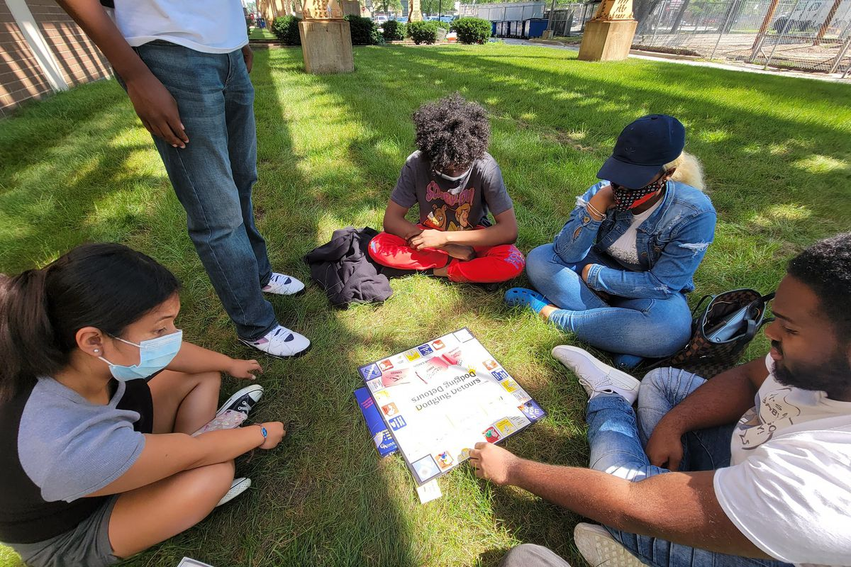 Students sit and play a board game outdoors, each wearing protective masks