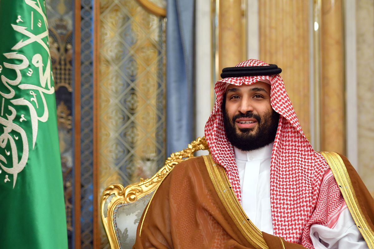 The crown prince, in traditional headscarf and robes, sits in a gold-backed chair with a Saudi flag nearby.