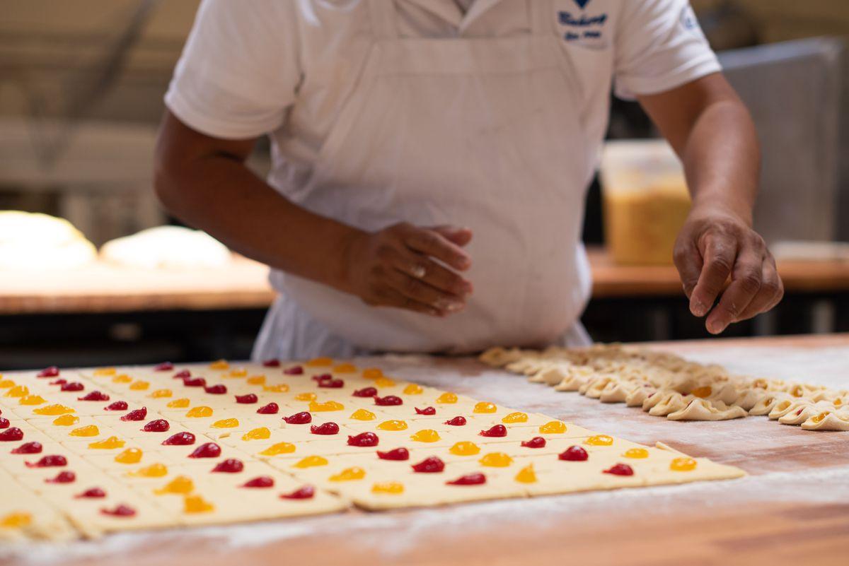 Một công nhân bọc bột xung quanh bánh quy với mứt bên trong của một tiệm bánh cũ.