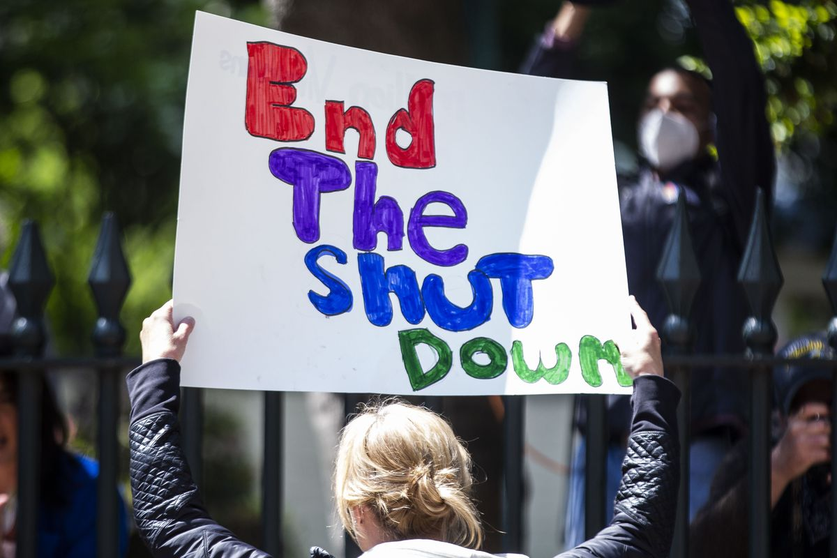 """A person holds up a sign that reads """"End the shut down."""""""