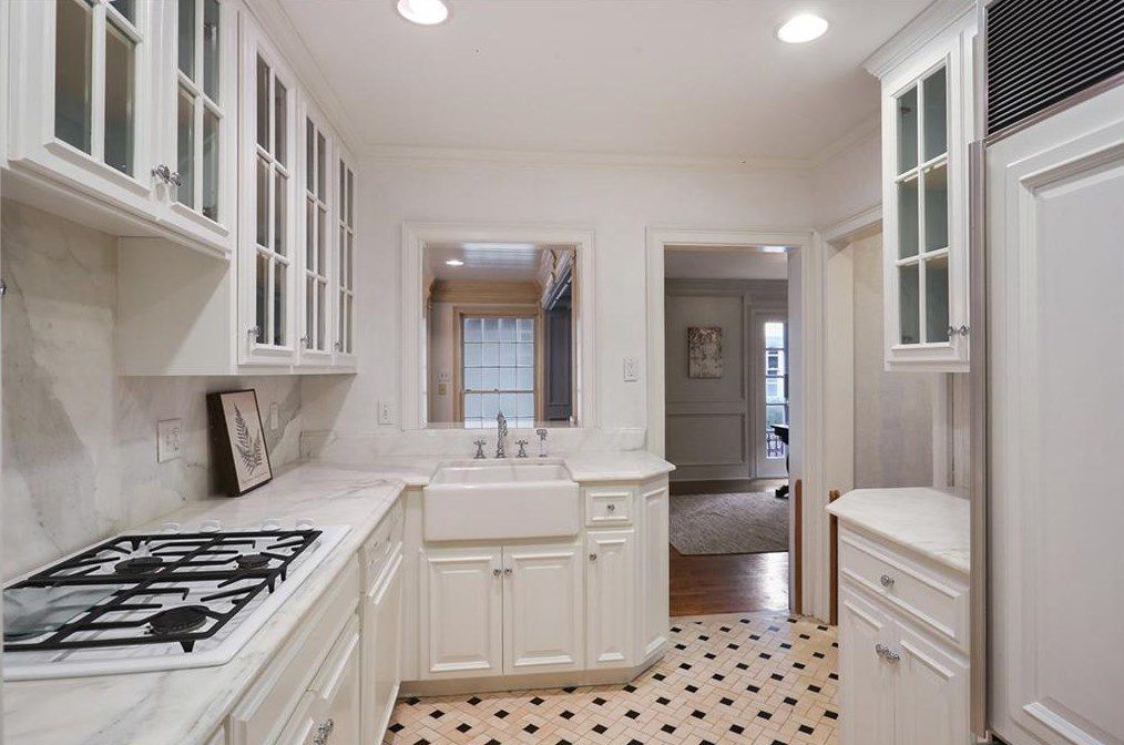 A white kitchen with tile and marble counters.