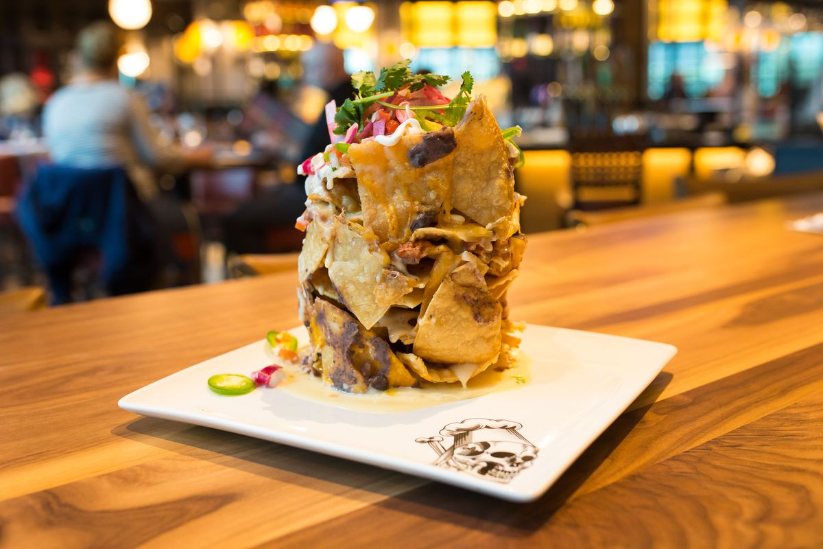 """A pile of """"trash can nachos"""" on a white plate on a wooden table in a restaurant"""