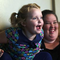 """In this photo taken Monday, Sept. 10, 2012, seven-year-old beauty pageant regular and reality show star Alana """"Honey Boo Boo"""" Thompson speaks during an interview as her mother June Shannon looks on in her home in McIntyre, Ga. The round-cheeked second-grader, who previously appeared on the TLC show """"Toddlers & Tiaras,"""" has a penchant for outrageous catchphrases as seen on her reality TV show, """"Here Comes Honey Boo Boo."""""""