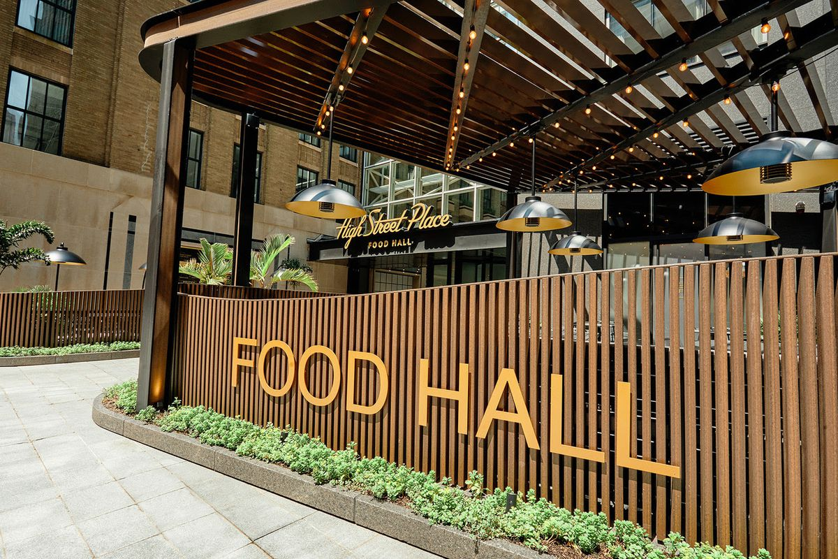 A fence made of dark wooden slats has orange lettering on it that reads food hall in capital letters.