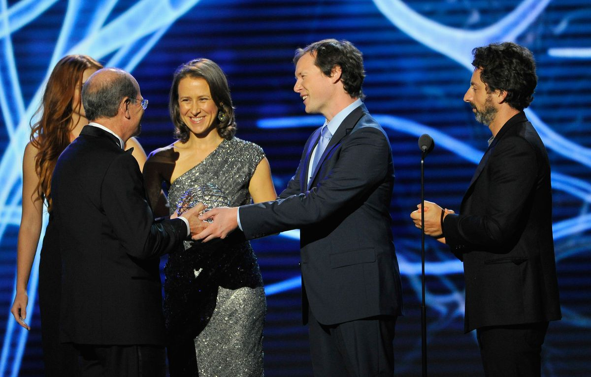 Neurosurgeon Alim-Louis Benabid, 23andMe's Anne Wojciki, patient Nicolas Berben and Google's Sergey Brin onstage at the 2015 Breakthrough Prizes ceremony.