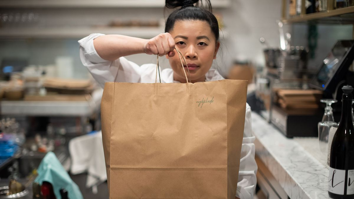 Nightshade owner and chef Mei Lin holds a brown bag of takeout inside her LA restaurant.