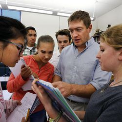 Teacher Syd Lott, second from right, helps students as they prepare for a test in IB Economics class at Skyline High School in Salt Lake City, Tuesday, Oct. 20, 2015.
