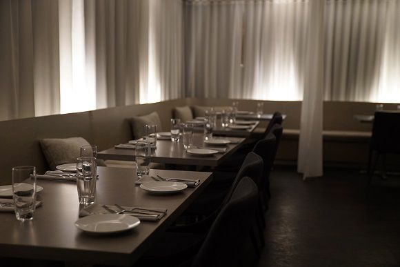 The dining room at Dessous features low lighting and white ethereal curtains.