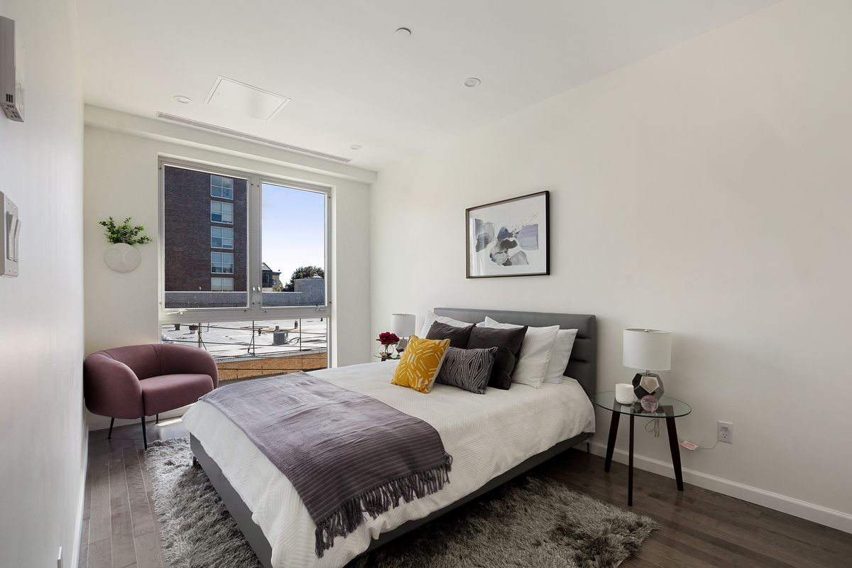 A bedroom with a medium-sized bed, large windows, and hardwood floors.