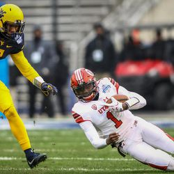 Utah Utes quarterback Tyler Huntley (1) slips and falls during the first drive of the game  while West Virginia Mountaineers safety Kenny Robinson (2) chases him down at the Zaxby's Heart of Dallas Bowl between the Utah Utes and the West Virginia Mountaineers in Dallas Texas on Tuesday, Dec. 26, 2017.