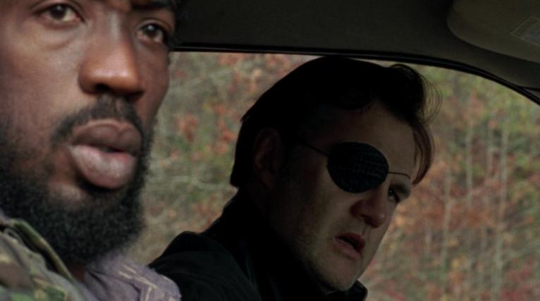 Two men are in a car. One of the men has an eye patch.