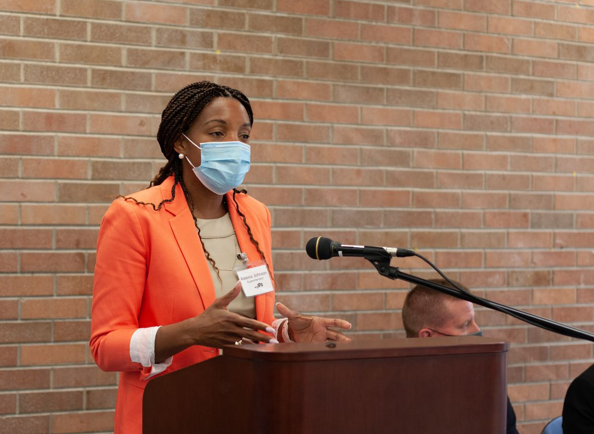 A woman in a formal bright orange jacket and a beige shirt wearing a blue face mask gestures with her hands as she speaks into a microphone at a podium in front of a red brick wall