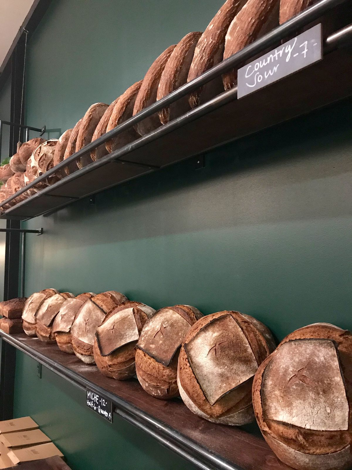 Two shelves of freshly baked loaves of bread at Evergreen Butcher and Baker in Kirkwood Atlanta