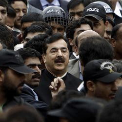 Pakistani Prime Minister Yousuf Raza Gilani, center, surrounded by guards, leaves the Supreme court following a hearing in Islamabad, Pakistan, Thursday, April 26, 2012. The Supreme Court convicted Gilani of contempt on Thursday for refusing to reopen an old corruption case against President Asif Ali Zardari, but spared him a prison term in a case that has stoked political tensions in the country. (AP Photo/Muhammed Muheisen)