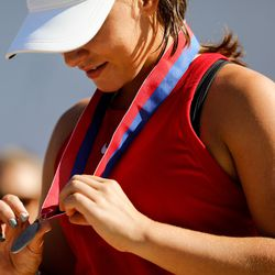 Erika Olsen, a senior at Bear River, looks at her medal after coming in second during the 4A girls singles tennis state tournament at Liberty Park Tennis Center in Salt Lake City on Saturday, Oct. 2, 2021.