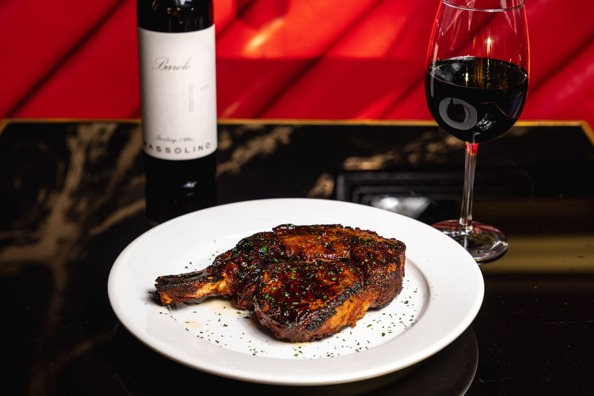 a ribeye steak on a plate, surrounded by a bottle and glass of red wine