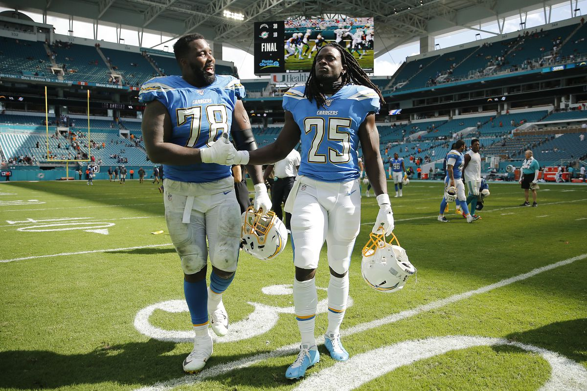 Trent Scott of the Los Angeles Chargers walks off the field with Melvin Gordon after the game against the Miami Dolphins at Hard Rock Stadium on September 29, 2019 in Miami, Florida.