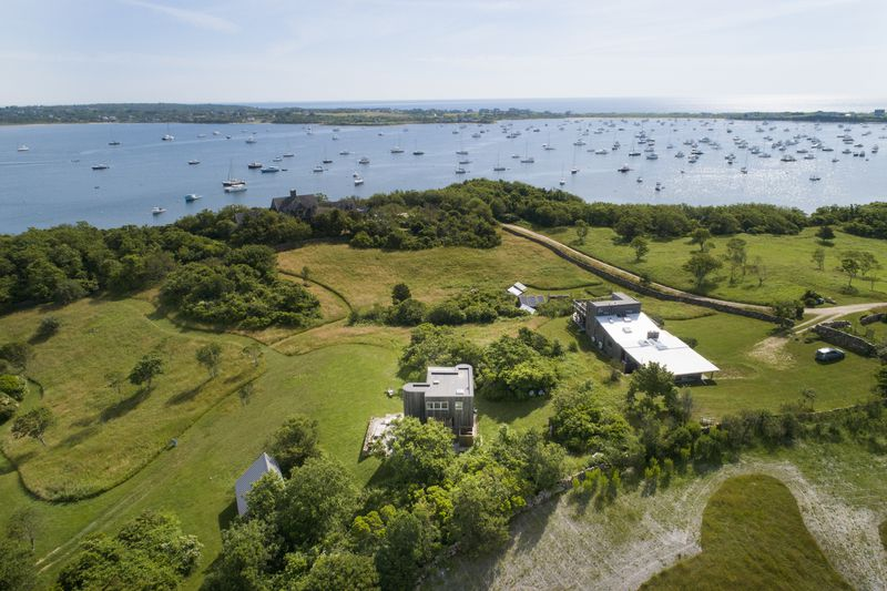 An aerial view of the home shows mature trees, a grassy lawn, and the ocean with boats on it in the distance.