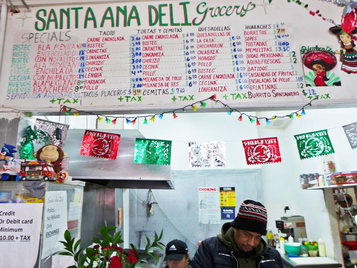 A white backdrop with red texts displays Santa Ana's menu in Bushwick.