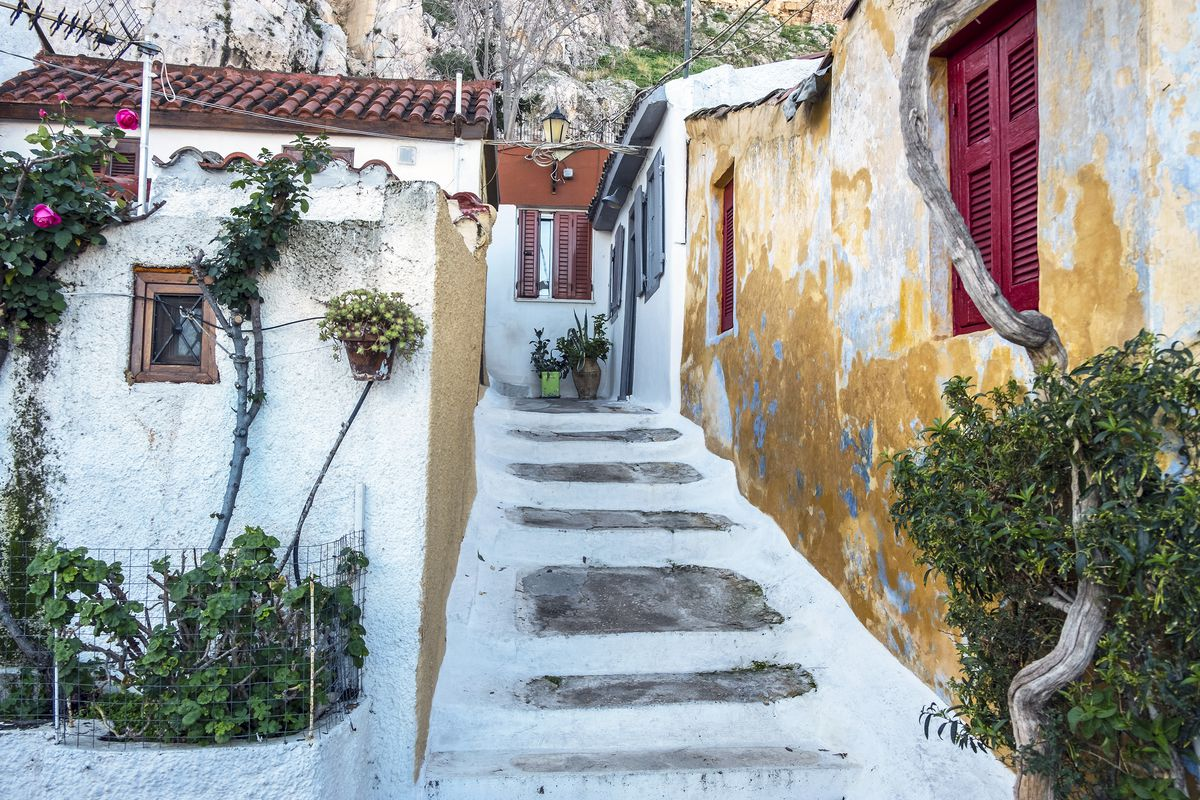 A street and houses in Athens, Greece. There is an ascending path lined by colorful walls.