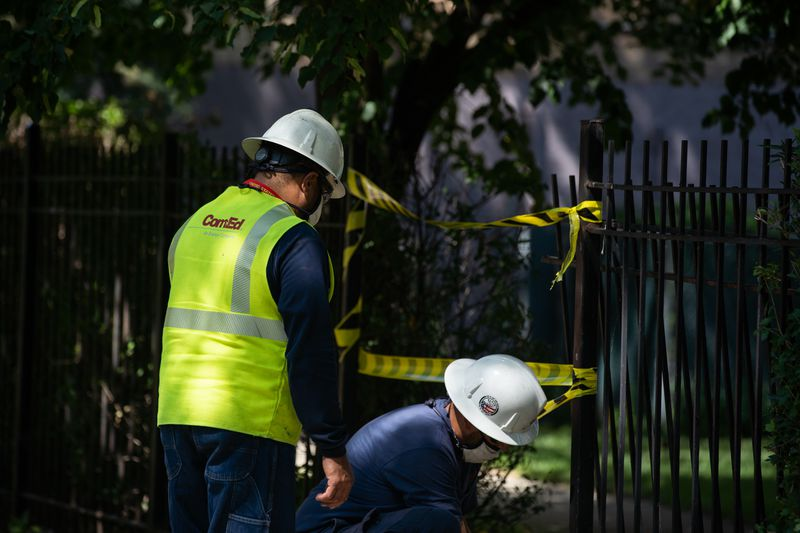 """ComEd workers fix a power outage in Uptown last August. The utility's """"smart grid"""" work has resulted in fewer outages."""