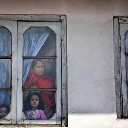 A Kashmiri Muslim family watches a protest against the U.S. in Srinagar, India, Tuesday, Sept. 18, 2012, as part of widespread anger across the Muslim world about a film ridiculing Islam's Prophet Muhammad.