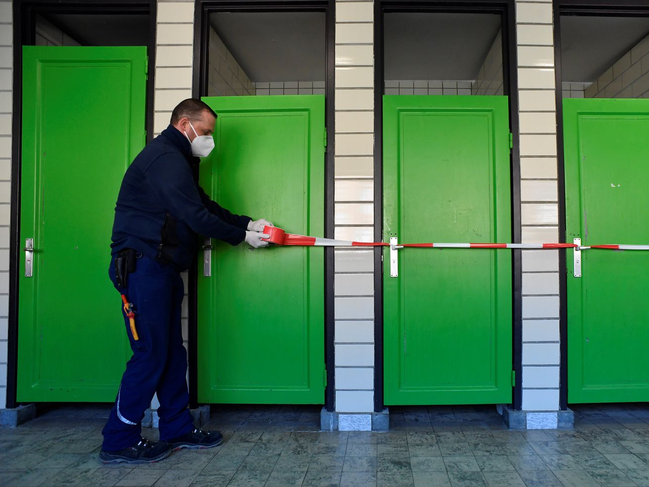 A man installs caution tape in front of bathroom stalls with green doors.
