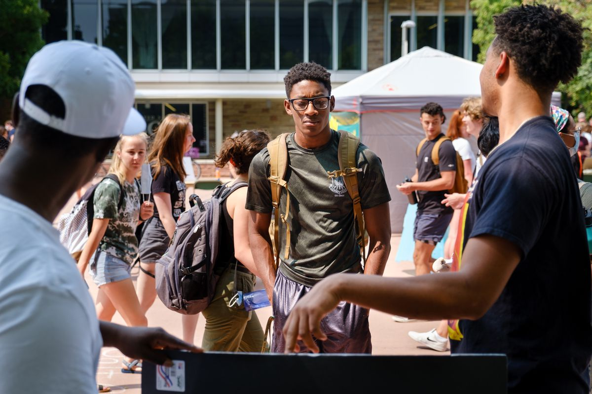 Two young men speak with another student about their on-campus organization as many other students walk behind him.