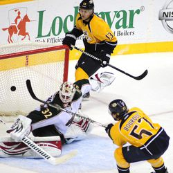 Nashville Predators forward Gabriel Bourque (57) scores past Minnesota Wild defenseman Mike Lundin (2) as the Predators center Nick Spaling (13) looks on during the second period of an NHL hockey game on Tuesday, April 3, 2012, in Nashville, Tenn.