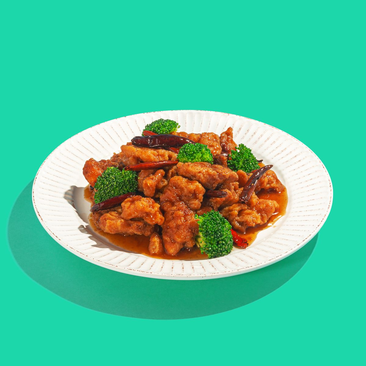 A white plate on a green background with pieces of orange chicken, dried red chiles, and broccoli