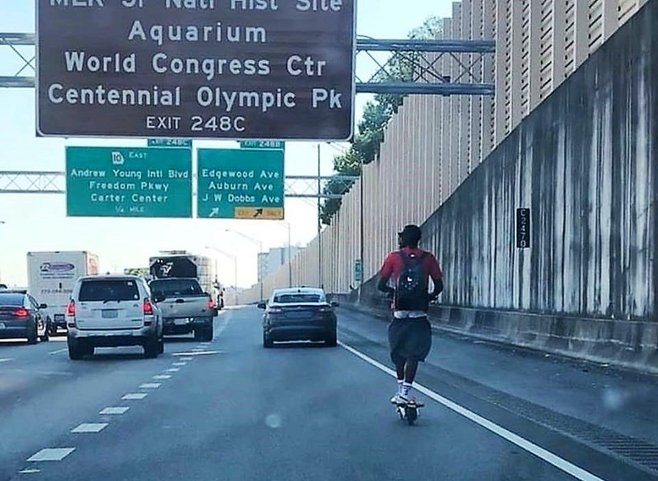 A photo of a man riding a Bird scooter on the highway