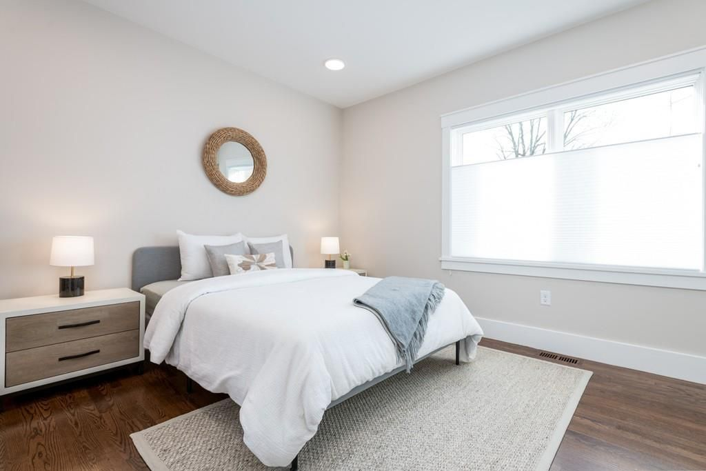 A bedroom with a bed, a long window, and a nightstand.