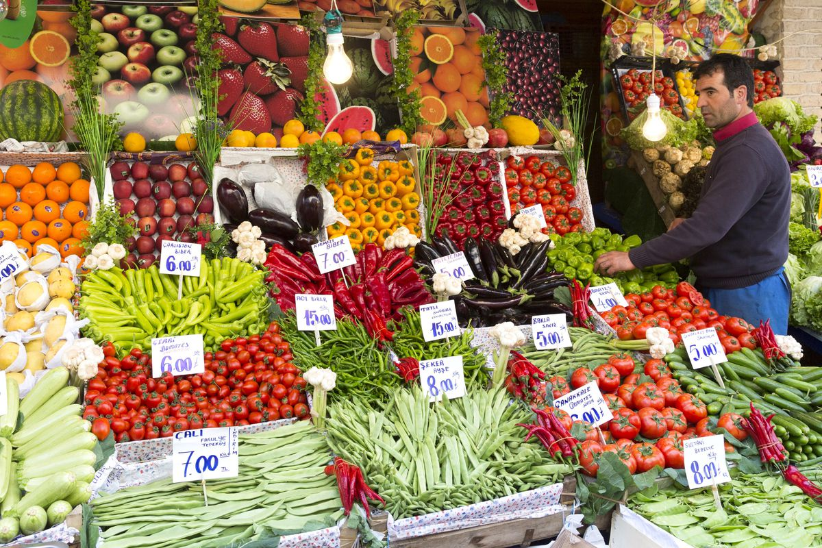 A shopkeeper surveys fresh fruit and vegetables at a food market in Istanbul.