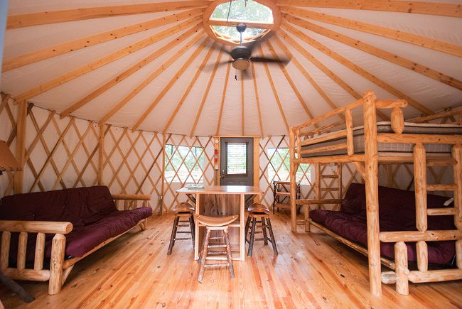 The interior of a large tent that has bunk beds, chairs, and a table.