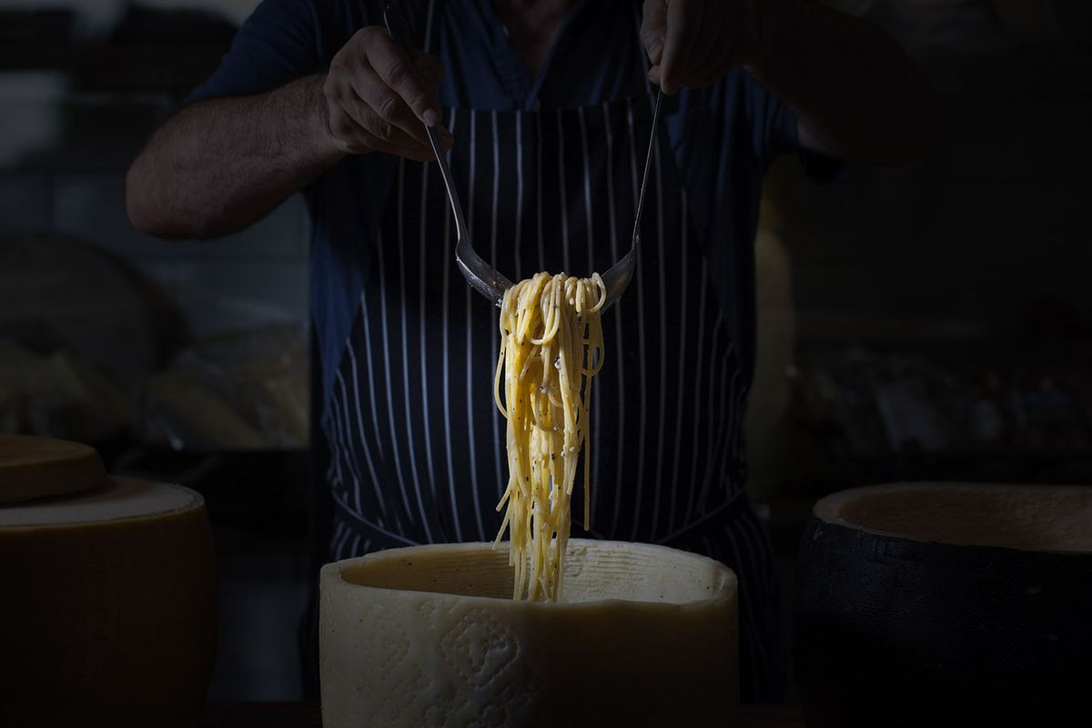 Two hands pull up pasta from the center of a cheese wheel.