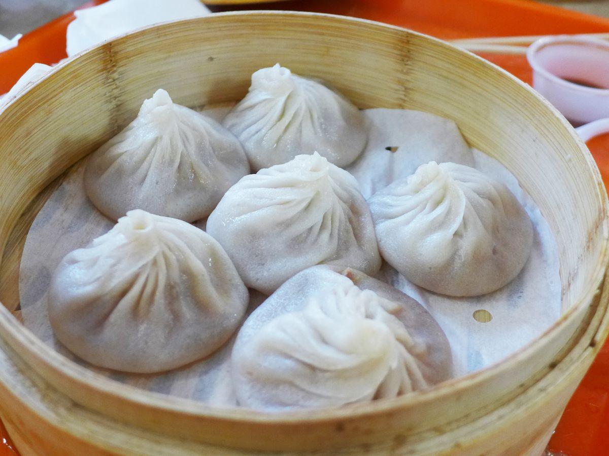 Six pork soup dumplings arranged in a bamboo steamer
