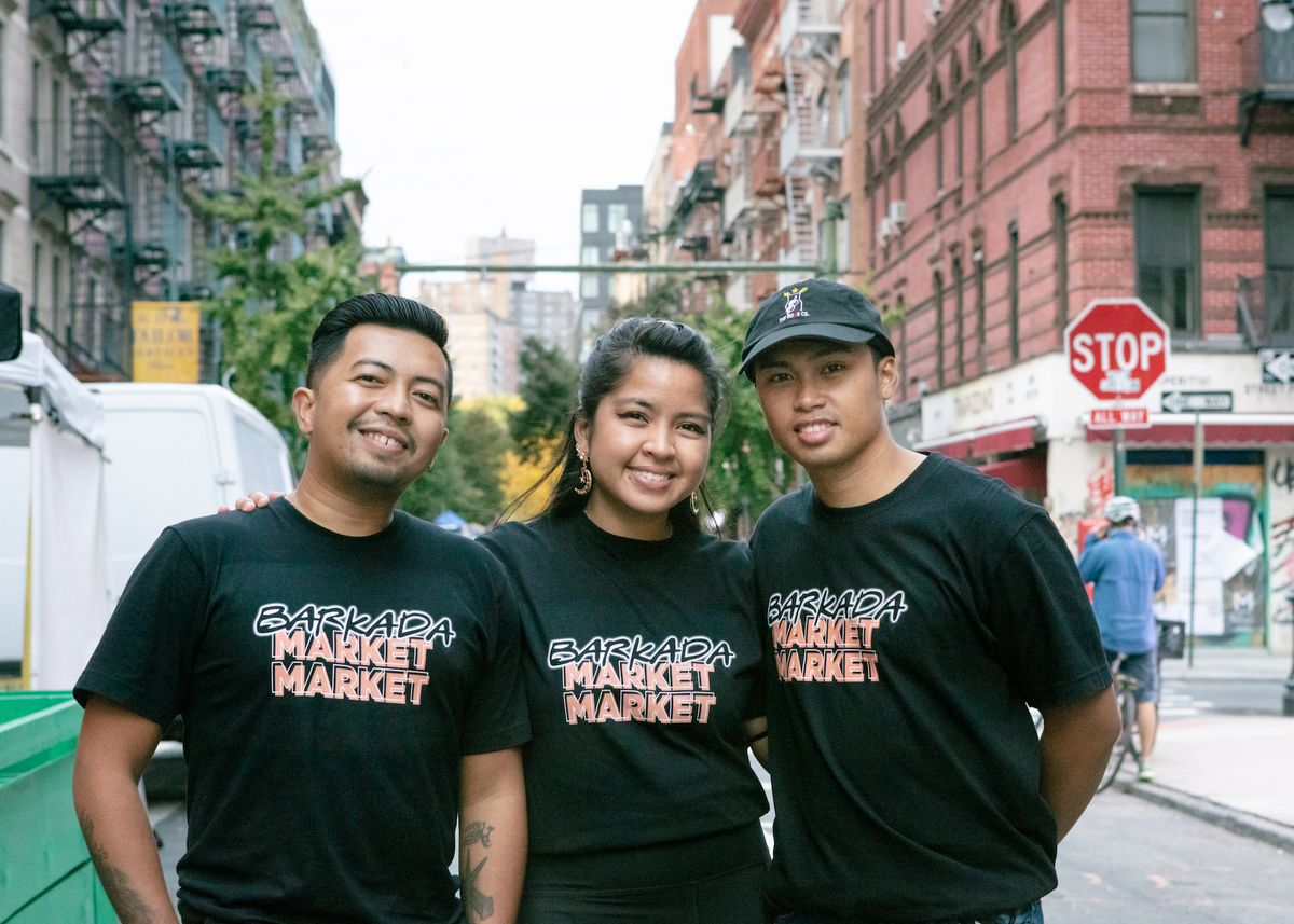 Three people wearing black t shirts and pants smiling and looking at the camera
