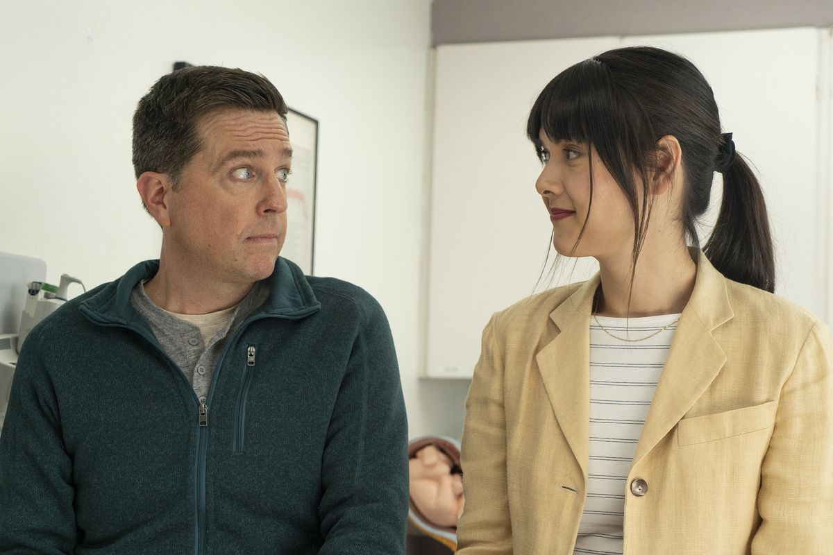 A middle-aged man and a younger woman look at each other with bemusement.