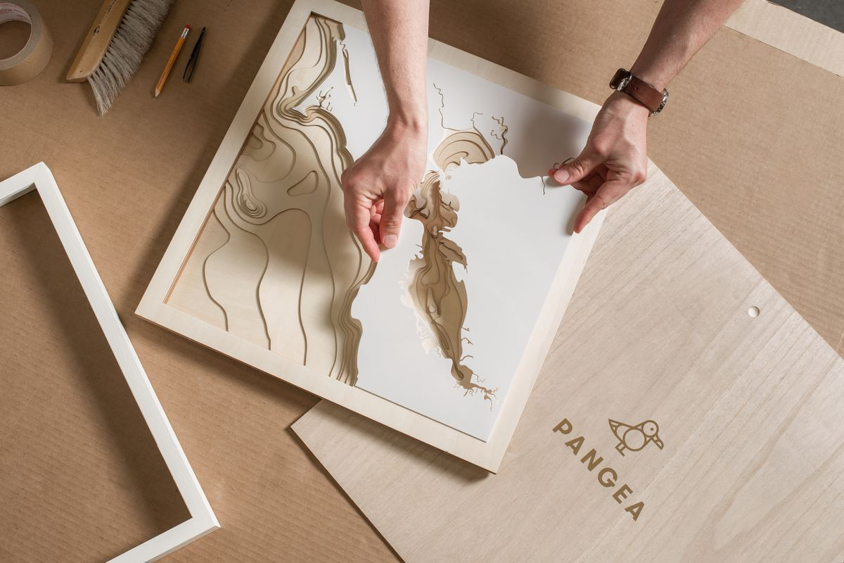 Aerial shot of man placing a piece of the map into a wooden box.