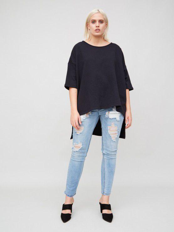 A model in a boxy T-shirt with an asymmetric hem
