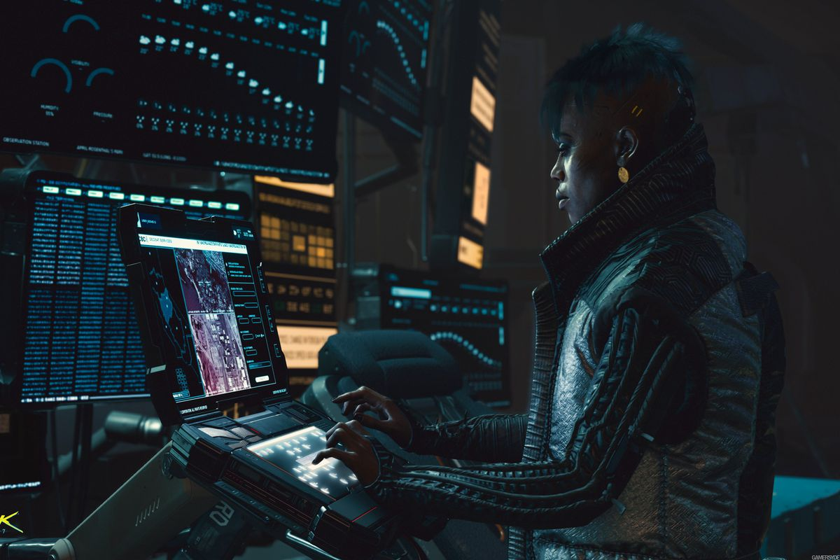 A woman uses a computer in a screenshot from Cyberpunk 2077
