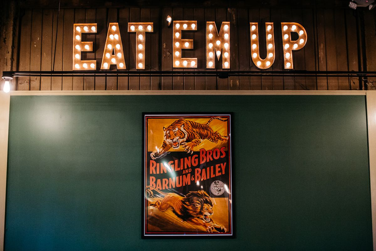 A neon sign on the wooden green wall says Eat 'Em Up. There's a poster from the Ringling Bros. & Barnum and Bailey circus, too