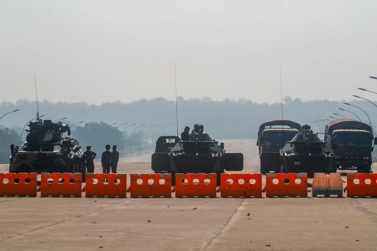 Myanmar's military stand guard at a checkpoint manned with an armored vehicles blocking a road leading to the parliament building Tuesday, Feb. 2, 2021, in Naypyitaw, Myanmar.