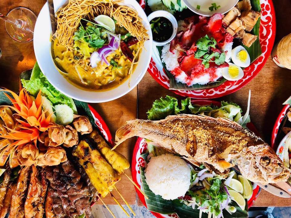 A selection of dishes, including a whole fried fish and meat skewers, at Bangrak Market